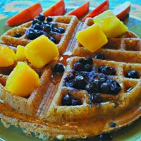 naked gluten-free vegan waffle with blueberries, mango, maple syrup