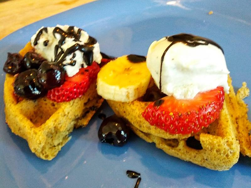 vegan waffles with chocolate syrup, strawberries, & coconut ice cream