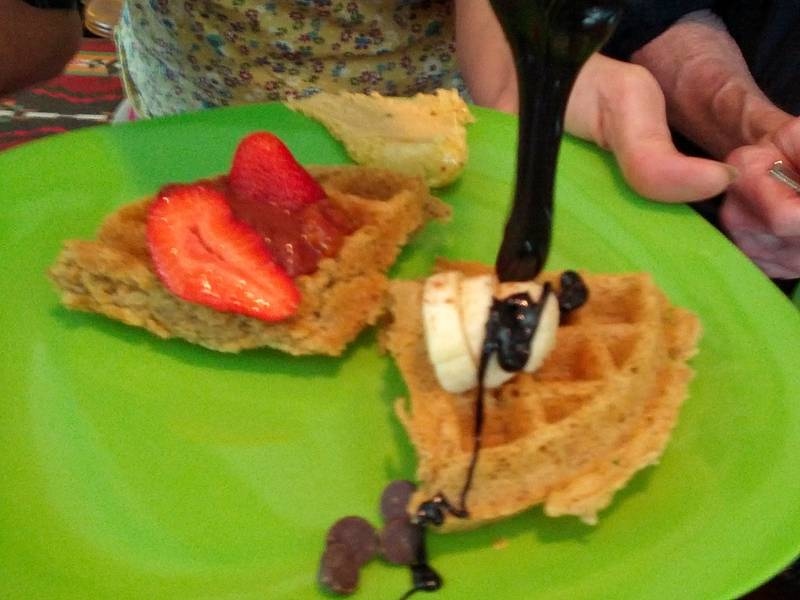 pouring thick chocolate sauce onto the vegan waffles