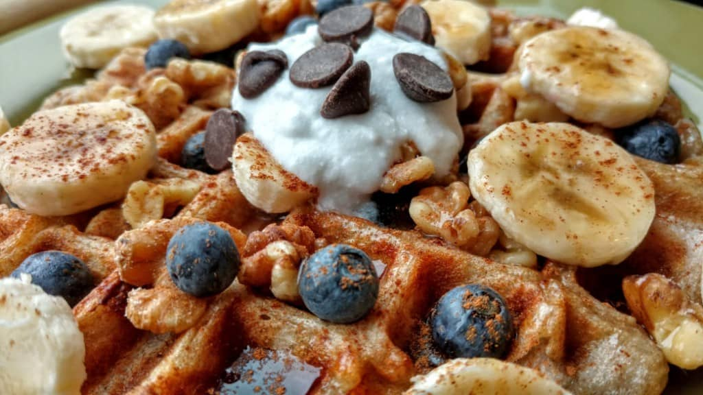 vegan sourdough waffles with blueberries, coconut cream, chocolate chips, side closeup