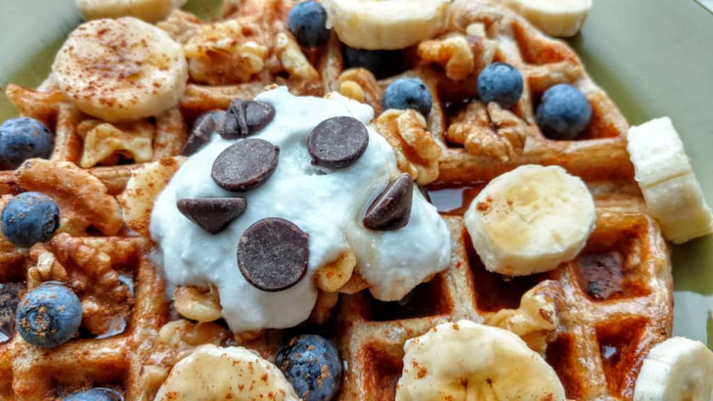 vegan sourdough waffles, with coconut cream, chocolate chips, cinnamon, and walnuts, closeup