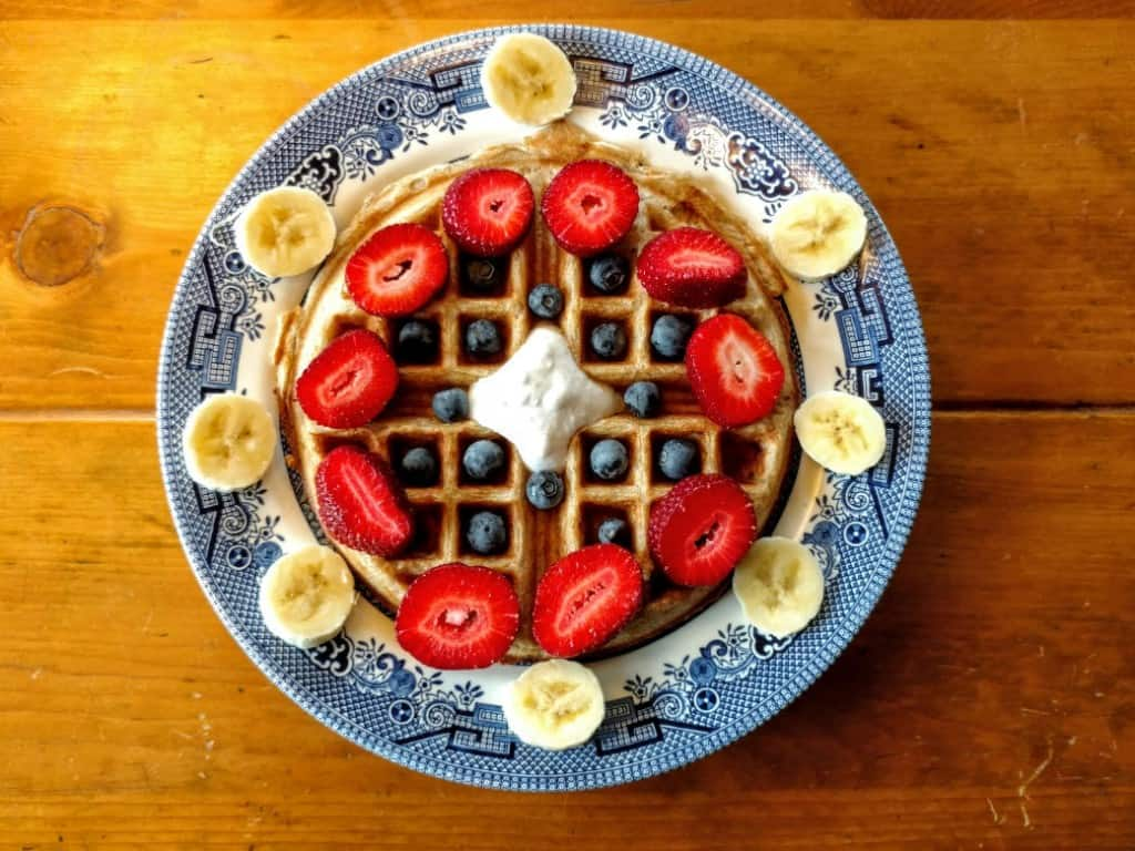 vegan sourdough waffles, overhead view, with strawberries, bananas, blueberries, and coconut cream