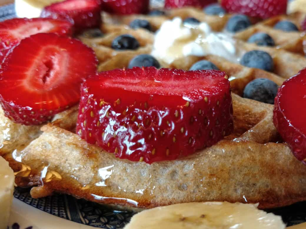 vegan sourdough waffles, closest side view, with strawberries, blueberries, coconut cream, and maple syrup