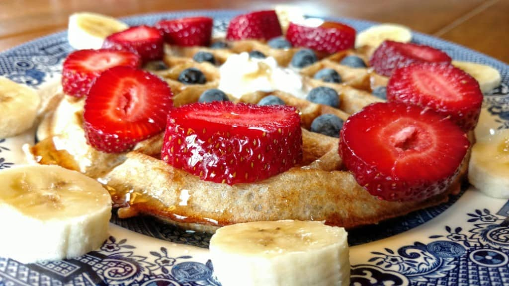 vegan sourdough waffles, side closeup view, with strawberries, blueberries, and banana