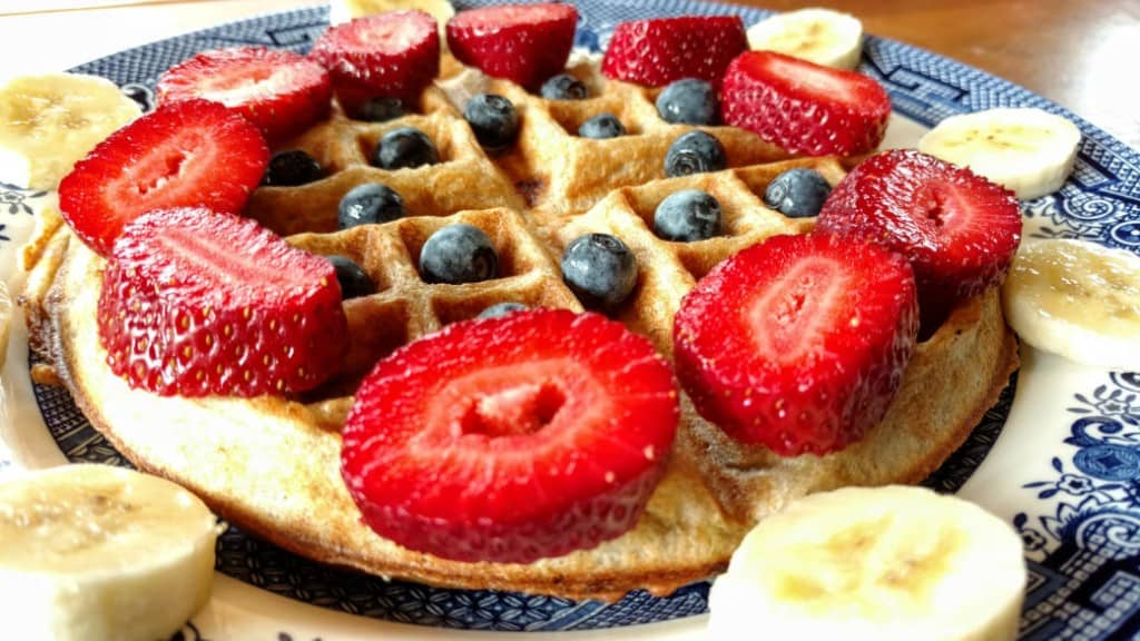 vegan sourdough waffles, side midrange view, with strawberries, blueberries, and banana