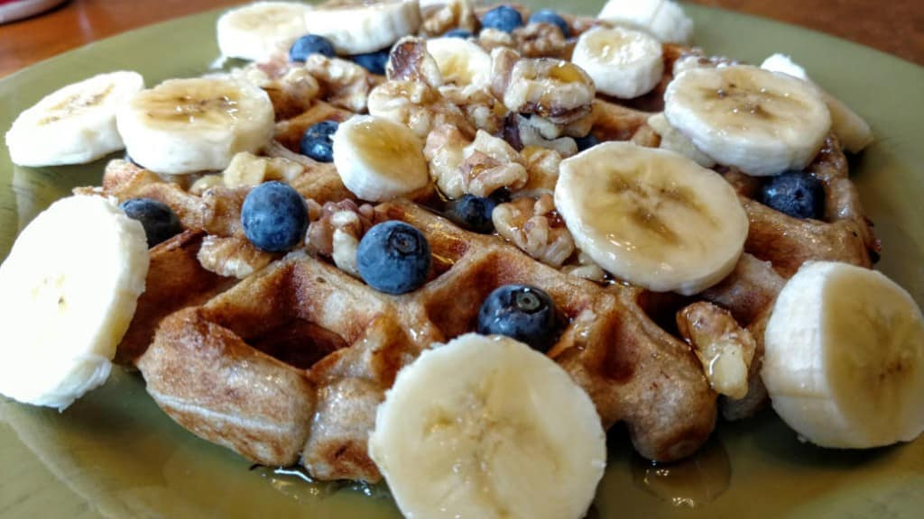 vegan sourdough waffles, side view, with blueberries, walnuts, bananas, and coconut cream