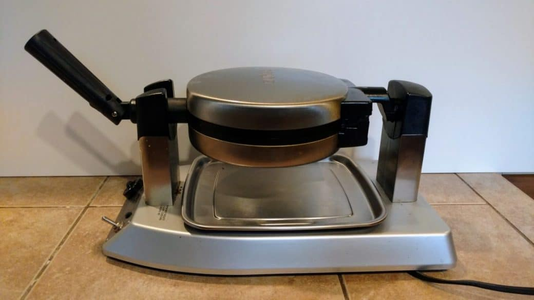 flip or rotating waffle maker in baking position batter already poured in
