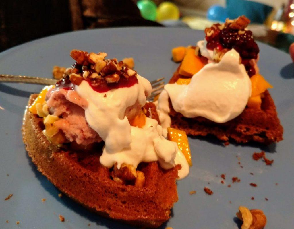 vegan waffles with ice cream, coconut, mango, nuts, marionberries