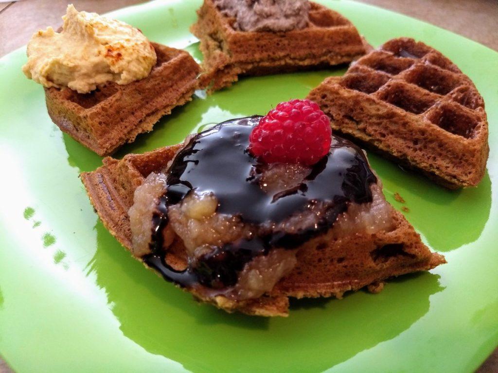 vegan waffles with waffle bar toppings: chocolate syrup, raspberry, hummus