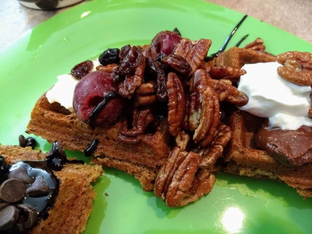 vegan waffles with waffle bar toppings: pecans, cherry, chocolate